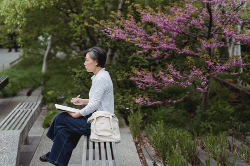 Woman in White Long Sleeve Shirt Sitting on Gray Wooden Bench Reading Book