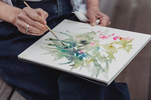 Person Holding White and Green Floral Painting