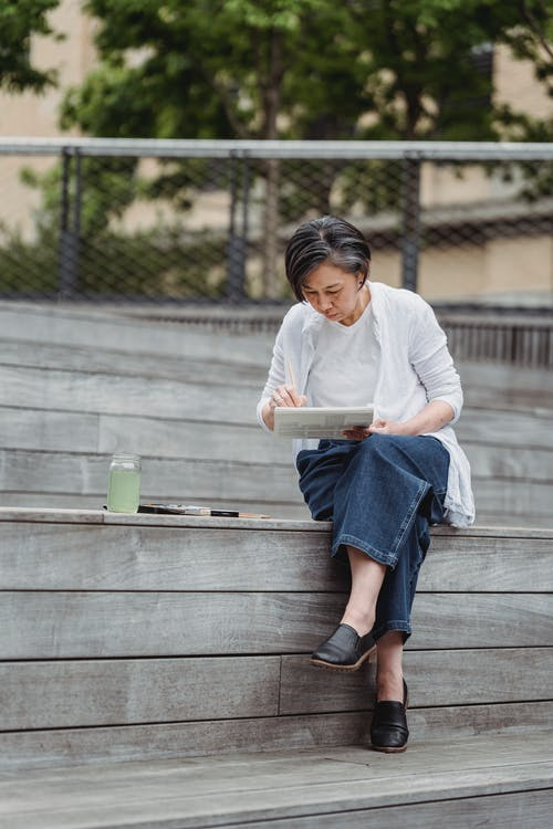 Man in White Long Sleeve Shirt and Blue Denim Skirt Sitting on Brown Wooden Bench during