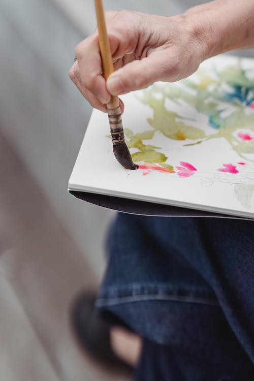 Person in Blue Denim Jeans Holding Brown Paint Brush