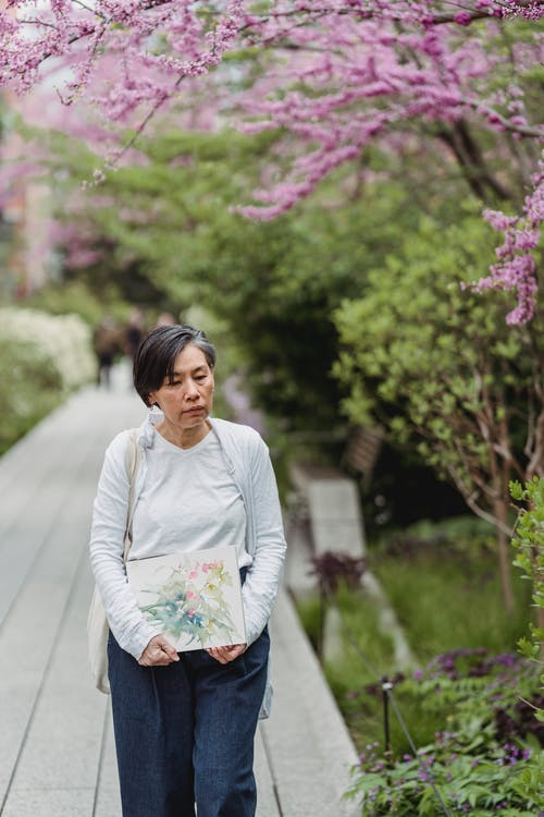 Woman in White Long Sleeve Shirt and Blue Denim Jeans Standing on Gray Wooden Pathway during