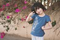 Girl In Blue Crew-neck T-shirt Next To Pink Petaled Flower