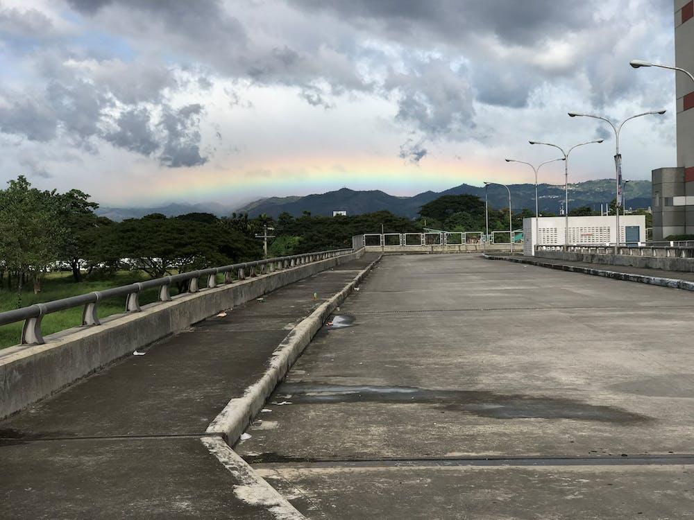 Darmowe zdjęcie z galerii z powyżej chmur, pusta droga, tęcza