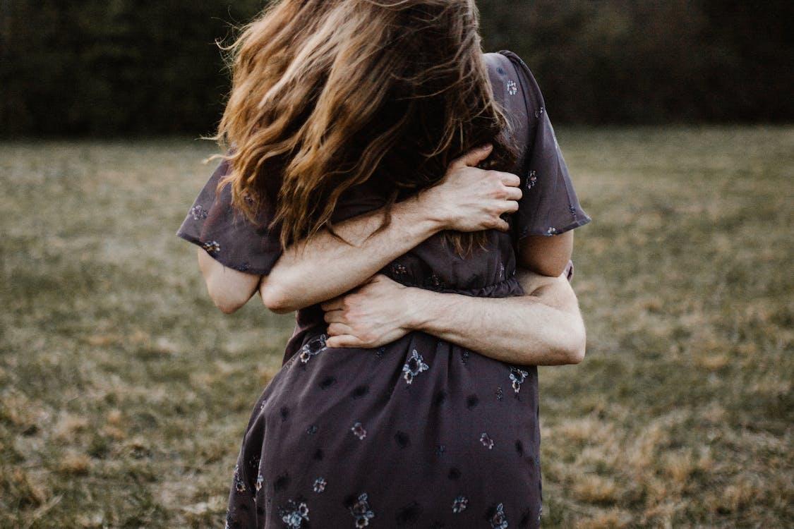 Woman in Black and White Polka Dot Dress Hugging Man in Black Shirt