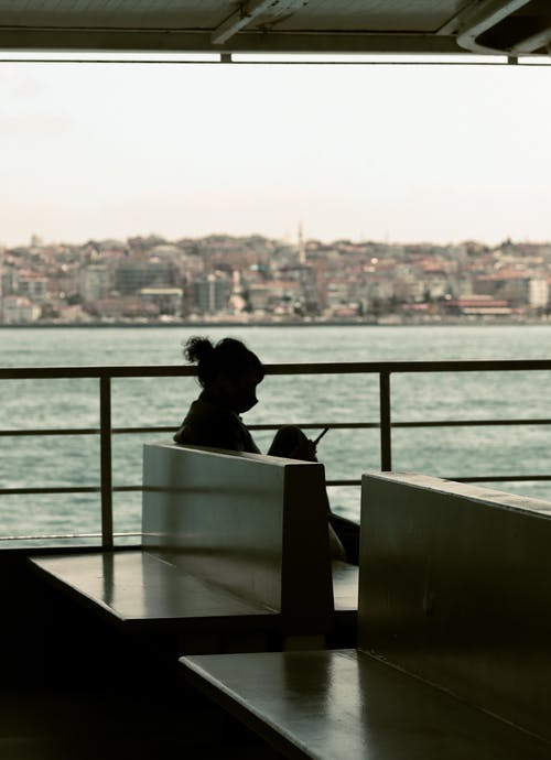 Woman Sitting on Chair Looking at the City