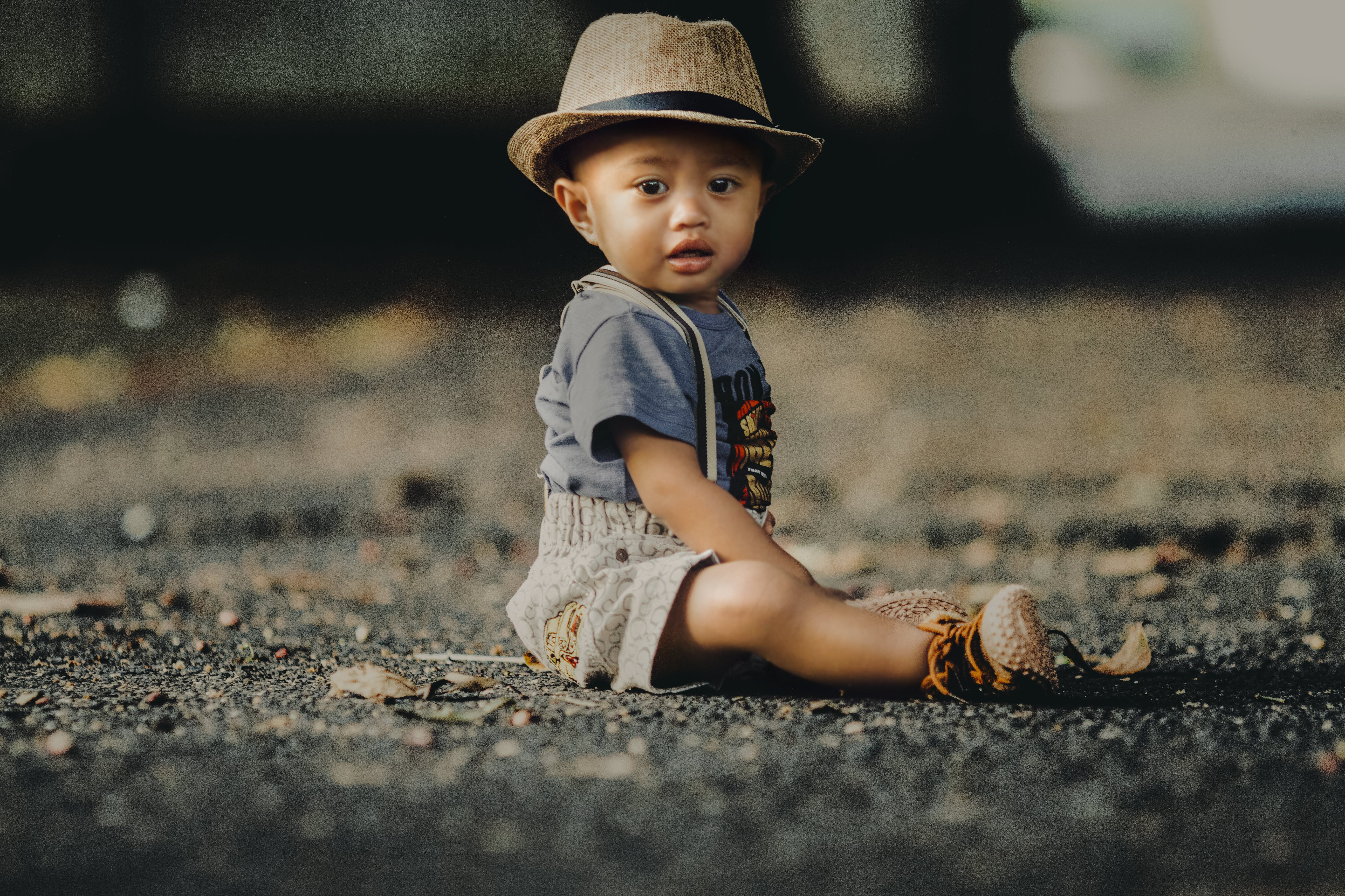 Child In Grey Shorts Sitting On Road