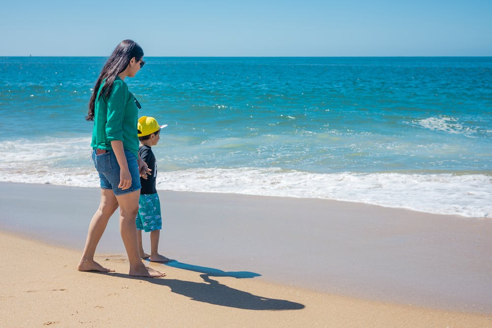 A woman and her son standing seashore.   Photo: Pexels