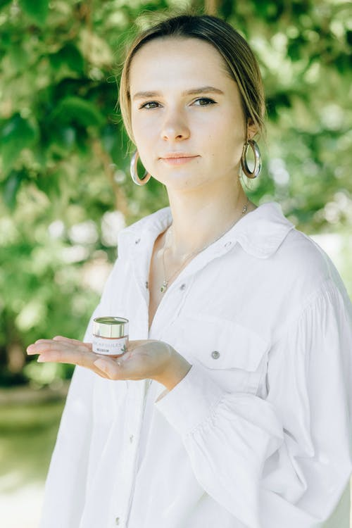 Woman in White Button Up Shirt Holding Clear Glass Cup