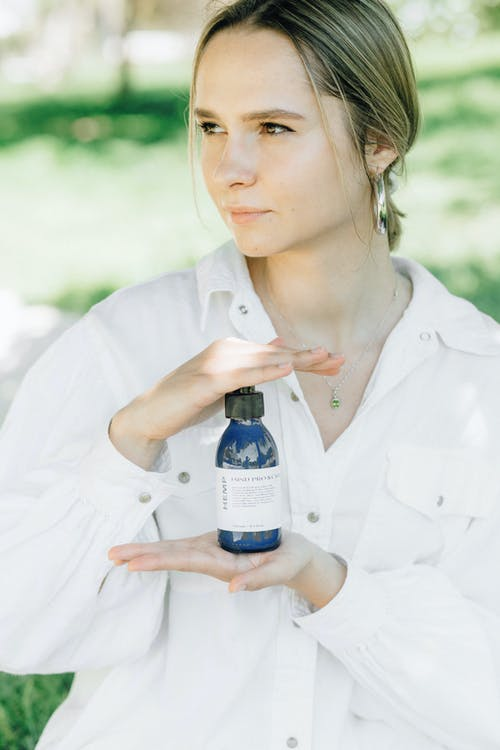 Woman in White Button Up Shirt Holding White Labeled Bottle