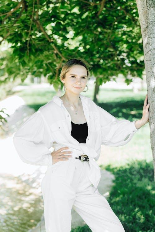 Woman in White Blazer Standing Beside Tree
