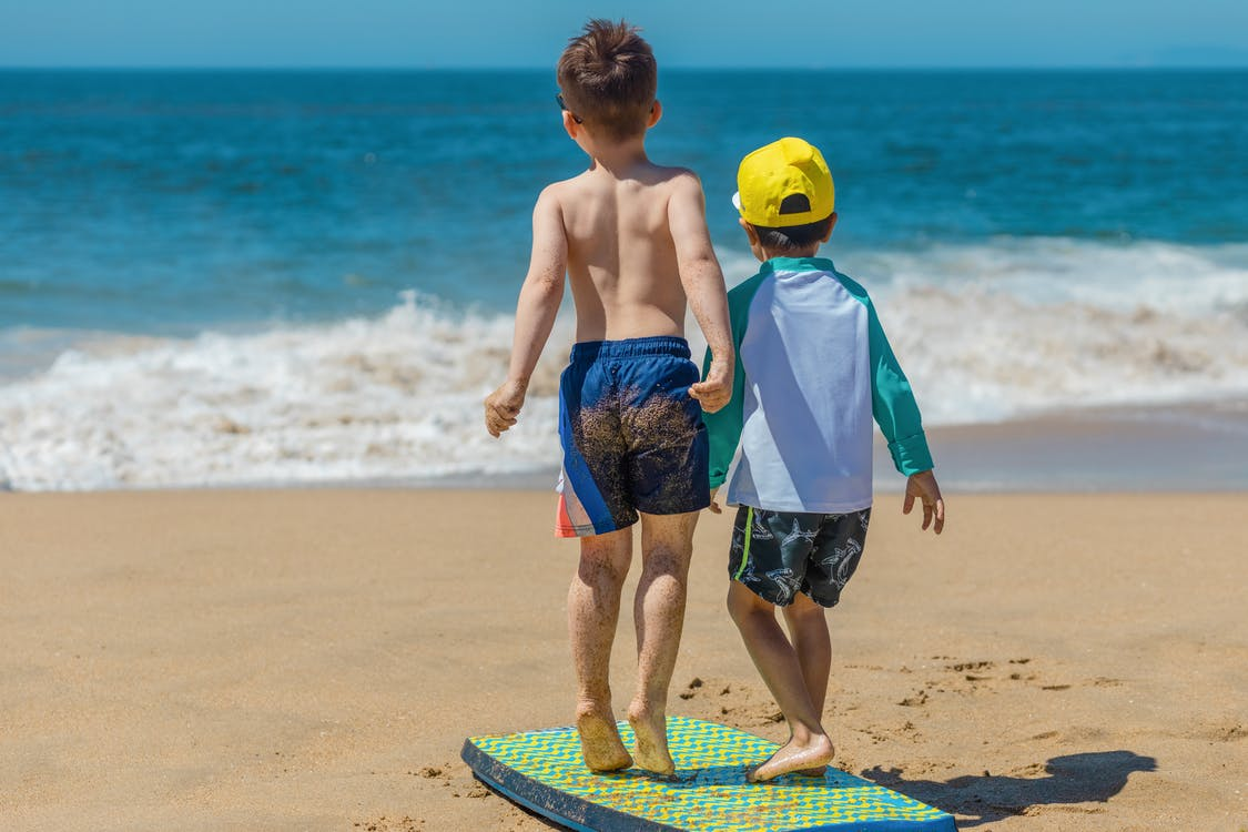 Man in Blue Shorts Holding a Child in Blue Shorts on Beach