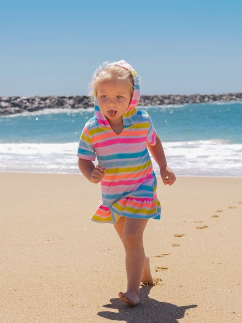 Girl in Green Pink and White Stripe Shirt Standing on Beach