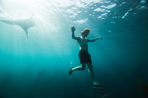 Woman in Blue Shorts Under Water