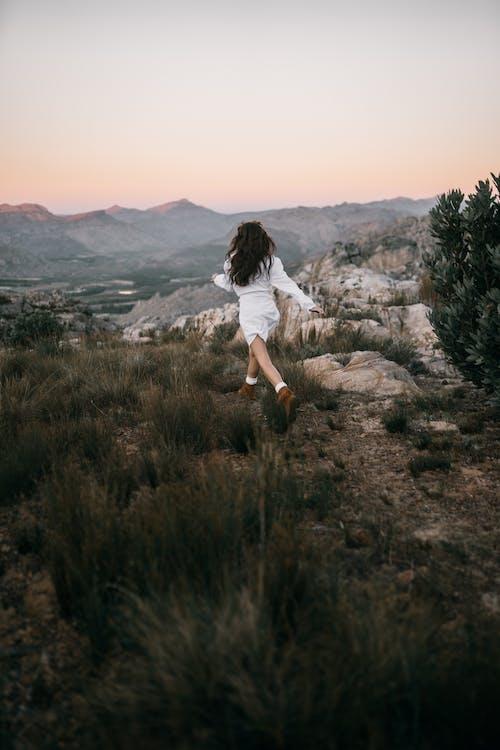 Woman in White Long Sleeve Dress Running