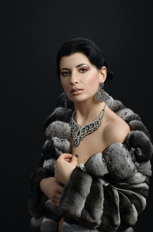 A Beautiful Lady Wearing a Gray Faux Fur Jacket and Expensive Accessories