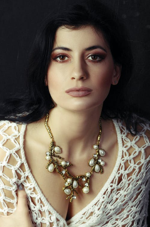 Woman Wearing a Gold with Pearl Necklace