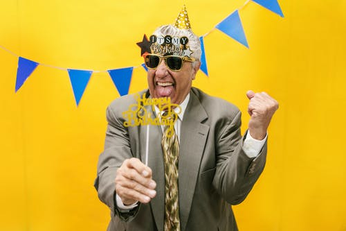A Cheerful Elderly Man in Gray Suit Celebrating His Birthday