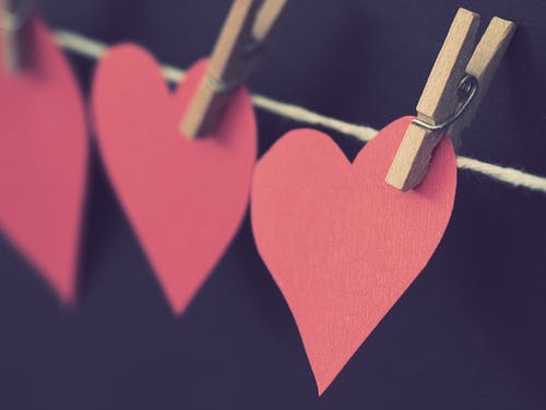 Photo of Red Heart-shaped Paper Hanging on Rope