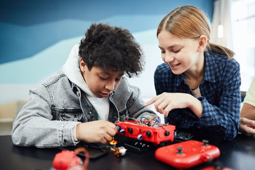Boy in Gray Jacket Playing Red and Black Toy Car