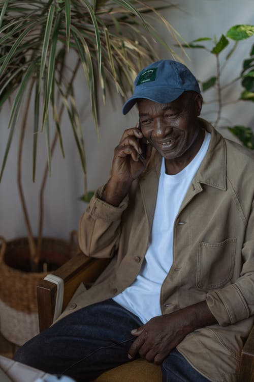 Photo of an Old Man Happily Talking on the Phone