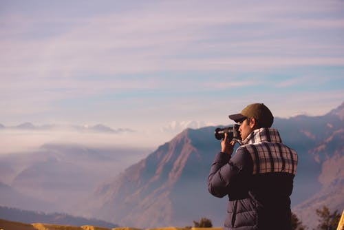 Male Photographer Taking Photos of Scenic Mountains