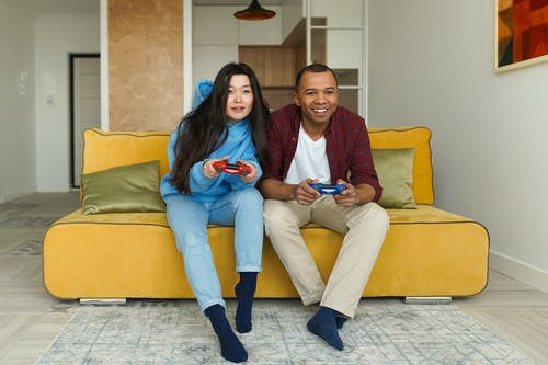 2 Women Sitting on Yellow Couch