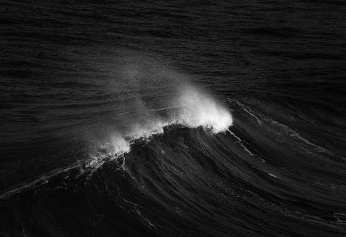 Black and white of huge wave of ocean in stormy winter weather in summer
