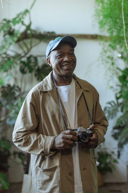 Photo of an Old Man Holding Camera