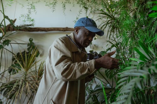 Man in Brown Coat Holding Black Dslr Camera