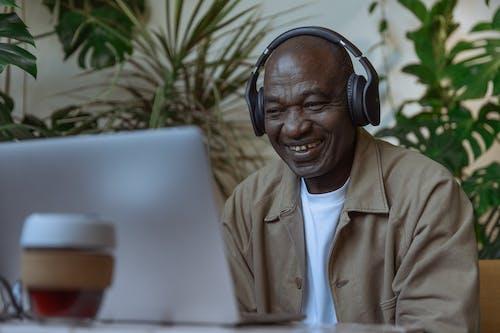 Man in Brown Button Up Shirt Wearing Black Headphones