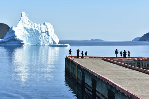 Iceberg Near a Dock with People