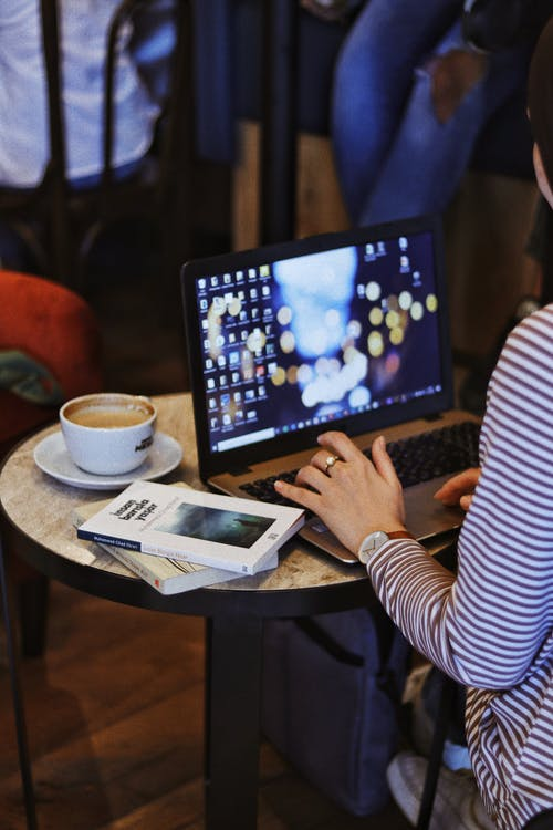 Crop anonymous female remote employee working on netbook at cafeteria table with books and cappuccino against people