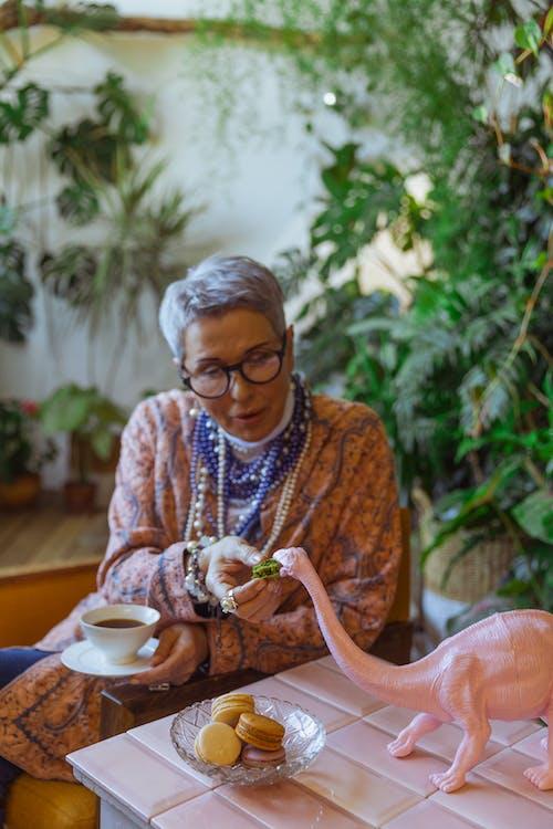 Photo Of Woman Feeding A Toy Dinosaur