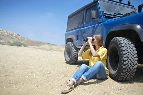 Woman Sitting on Soil Beside Jeep While Using Binoculars