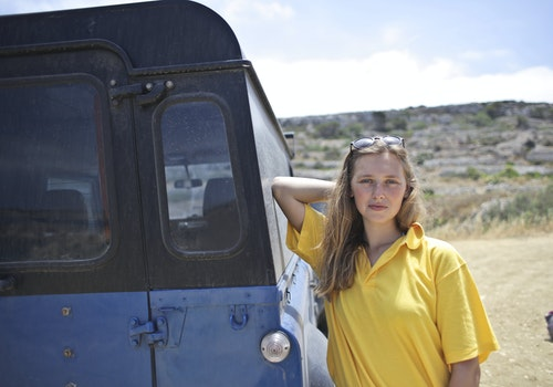 Woman Wearing Yellow Polo Shirt Leaning on Car