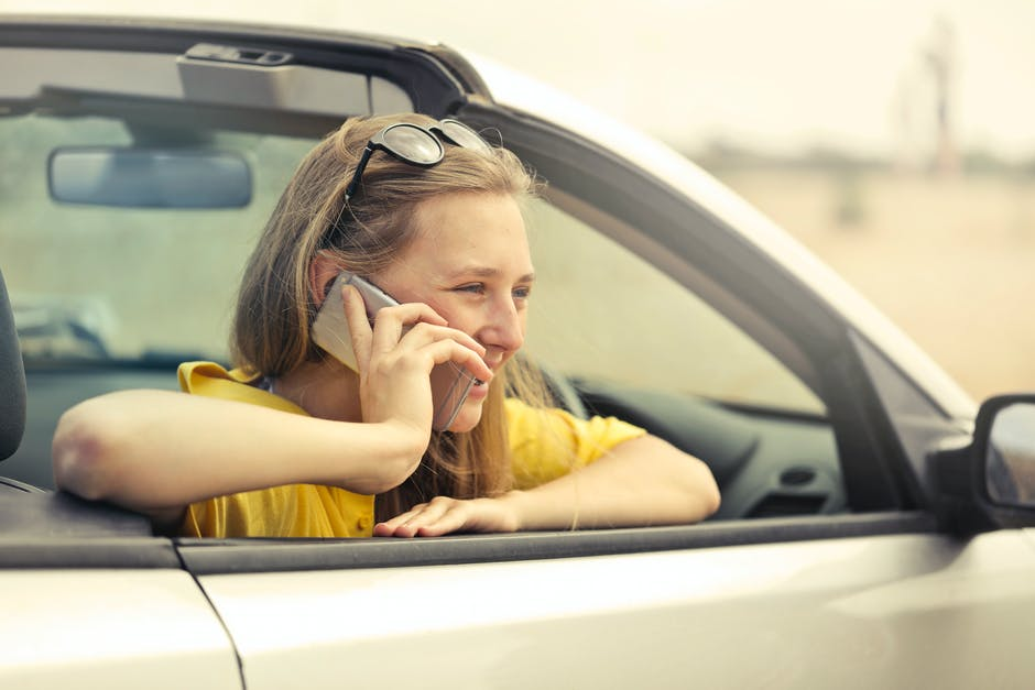 Blonde-haired Woman in Yellow T-shirt Wearing Black Sunglasses Holding Silver Smartphone