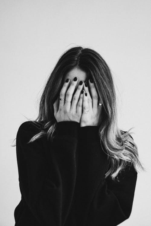 Grayscale Photo of a Woman Covering Her Face