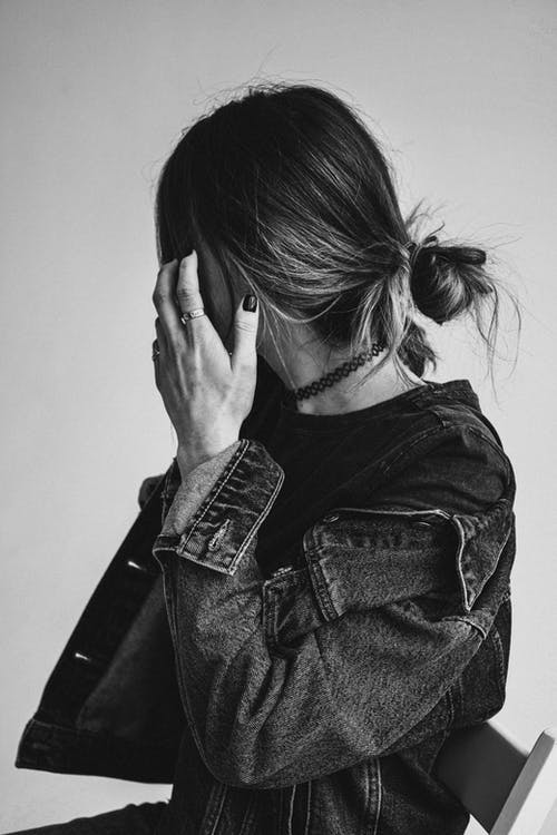 Woman in Denim Jacket Covering Face With Her Hair