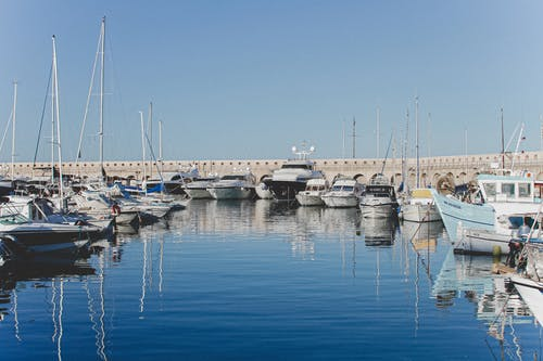 Bay with yachts and motorboats moored on calm water near concrete bridge on sunny day under blue sky