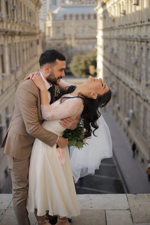 Loving newlyweds hugging on street