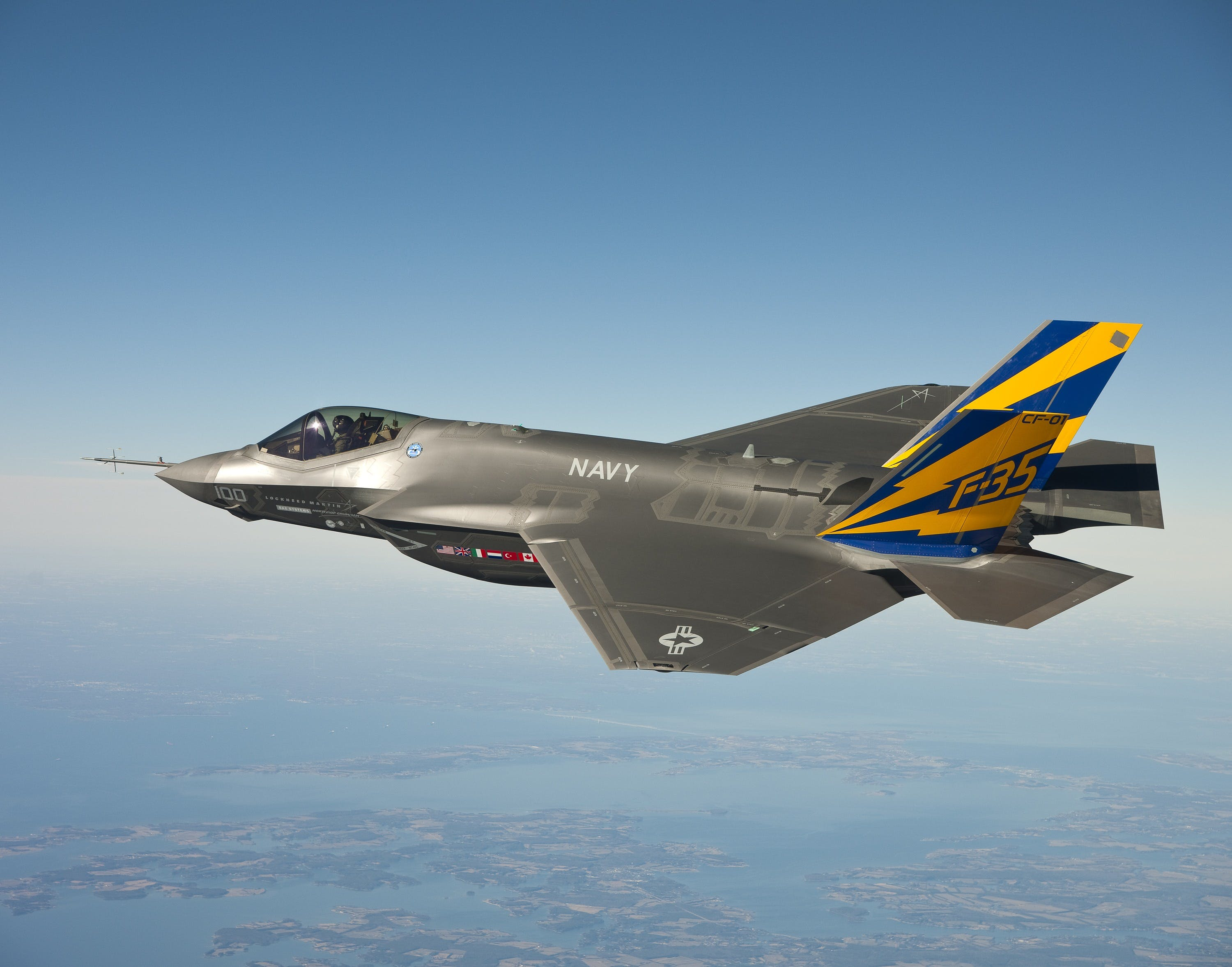 Grey Blue and Yellow Navy F 35 Fighter Plane Flying on Clear Blue Sky