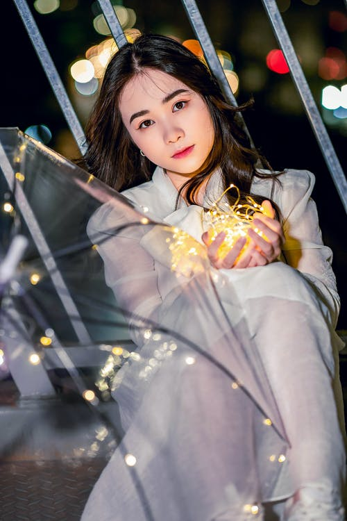Photo of a Beautiful Woman in a White Dress Holding String Lights