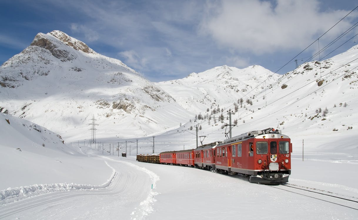 Red and Black Train Running Along Snow Covered Field
