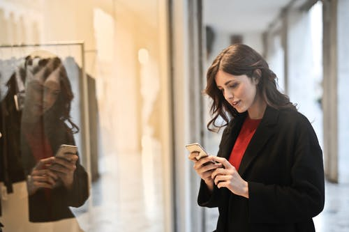 Close-up Photo of Woman in Black Coat Using Smartphone