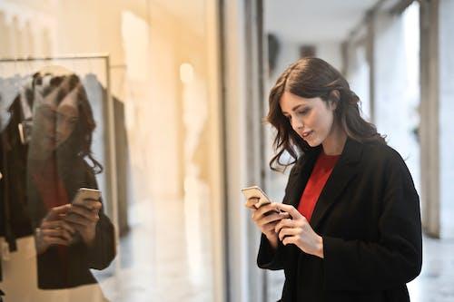 スマートフォンを使用して黒いコートを着た女性のクローズアップ写真
