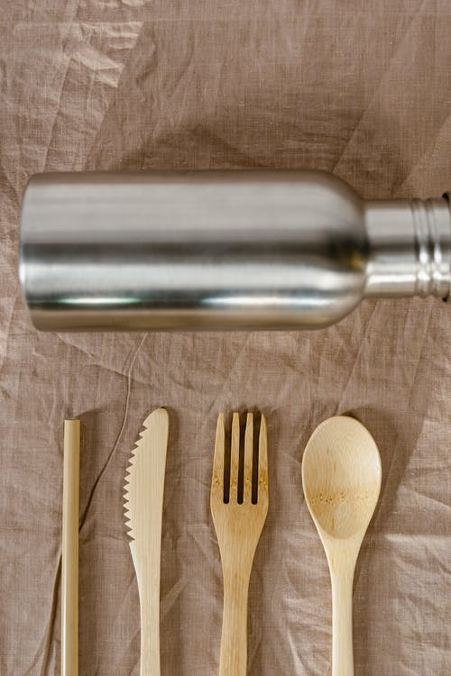 Stainless Steel Vacuum Flask Beside Brown Wooden Fork and Knife