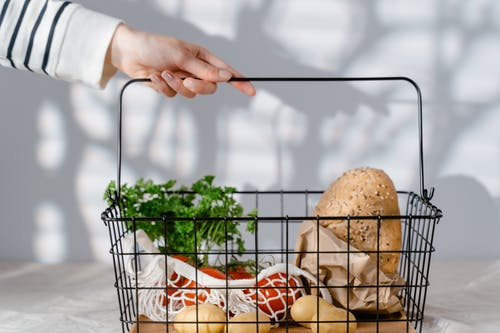 Person Holding Bread on Shopping Cart