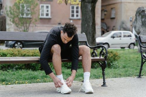 Man tying shoelaces on bench
