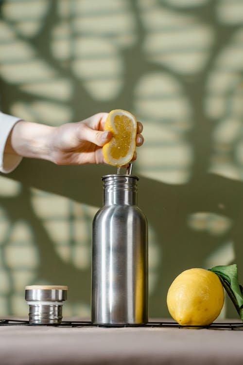 Person Holding Yellow Fruit and Stainless Steel Container