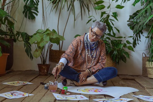 Photo Of Woman Sitting On Floor While Painting
